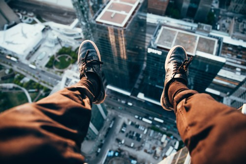 Guy-sitting-on-edge-of-building-with-feet-hanging-overlooking-the-city.jpg