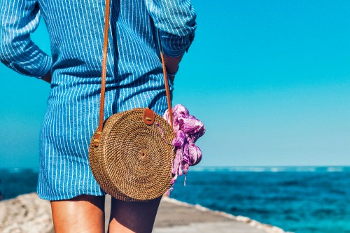 Woman-Wearing-Blue-and-White-Striped-Dress-with-Brown-Rattan-Cross-body-Bag-near-Ocean.jpg