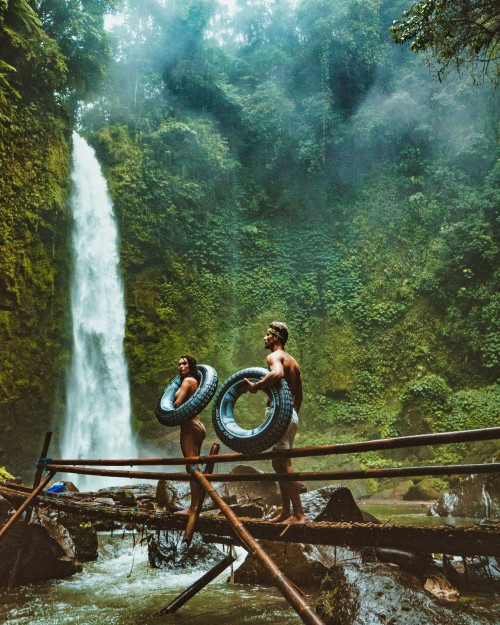 Two-People-Carrying-Black-Inflatable-Floats-walking-on-Brown-Wooden-Bridge-Near-Waterfall---man-woman-male-female.jpg
