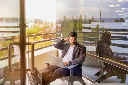 Man-Sitting-With-Laptop-on-Balcony.jpg