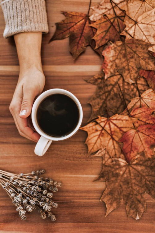Hand-Holding-Cup-of-Coffee-on-Table-with-Leaves.jpg